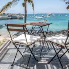 2 chairs and a small fold out table overlooking a beach