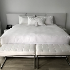 White room with large bed covered in white sheets