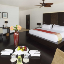 view of the inside of a pikaia lodge bedroom with bed, tv stand desk and coffee table